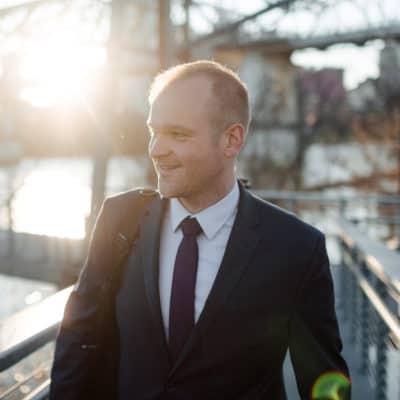 Photo of musician Ryan Middagh smiling while he walks on a bridge