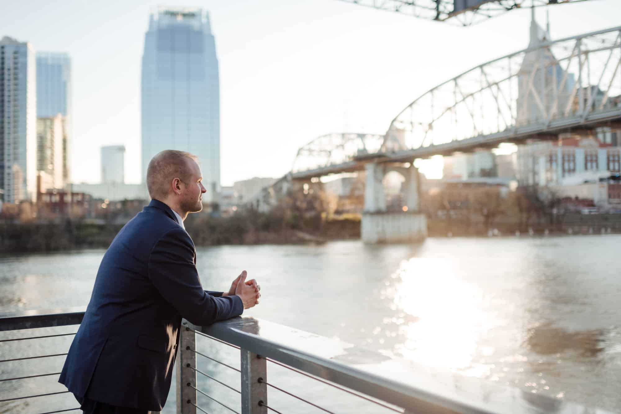 Photo of musician Ryan Middagh wearing a suit and leaning against a railing on a bridge