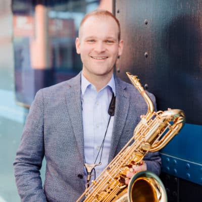 Photo of musician Ryan Middagh smiling and holding his saxophone